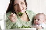 женщина ест салат и держит на руках ребенка