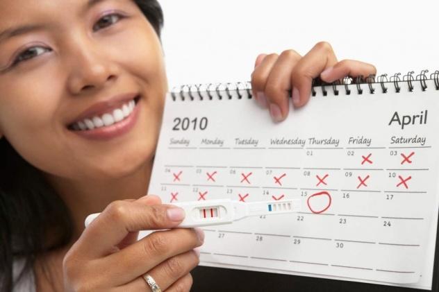 девушка держит календарь и тест